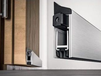 Imagem do Veda Porta Automático aplicada do lado externo da porta de madeira.